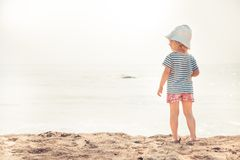 Lone child baby on beach looking into the sea horizon bright sunlight childhood lifestyle summer beach holidays background copy s. Pace stock photos