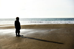 Lone child on a beach before sunset. Silhouette of a little boy on a beach  before sunset Royalty Free Stock Photo