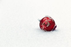 A lone Christmas toy thrown in the snow after a new year's celebration. End of Holidays. Royalty Free Stock Image