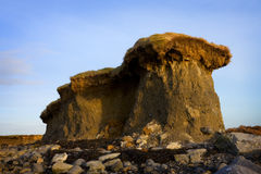 Lone cliff on stony beach Stock Images