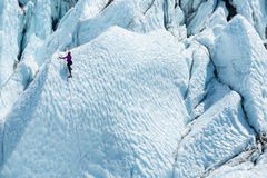Lone climber reached a top of one iceberg. Lone climber reached one ice peak, many peaks ahead Royalty Free Stock Images