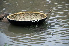 Lone Coracle. Newly built coracle decked with flowers with row stick Stock Photos
