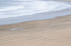 Lone couple walking along deserted beach Stock Photography