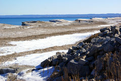 Lone explorer on a snowy rocky shoreline on a winter lake Royalty Free Stock Photos