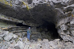 Lone Female Caver At Entrance To Large Cave. Caver at the entrance to large lava tube cave in California stock photography