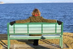 Lone female sitting on bench in the spring Royalty Free Stock Image