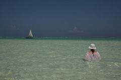 Lone figure on beach in Michamwi-Pingwe Zanzibar,. Lone figure on the beach viewed from the luxury Boutique Hotel Matlai in Michamwi-Pingwe, Zanzibar.  Sailing Royalty Free Stock Image