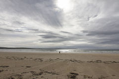 Lone Figure on an Empty Beach Stock Photo