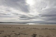 Lone Figure on an Empty Beach. A lone figure walks towards the sea across an empty beach Stock Photo