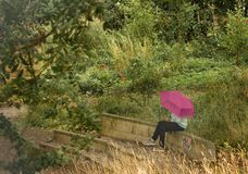 Girl with the pink umbrella. The lone figure of a girl checking her phone under a pink umbrella in Hirst Wood Nature Reserve, Yorkshire royalty free stock photography