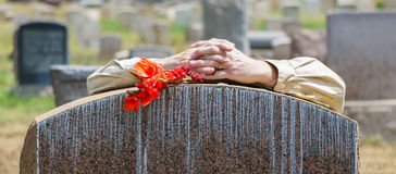 Lone Figure of Person Grieving at Cemetery Royalty Free Stock Photo
