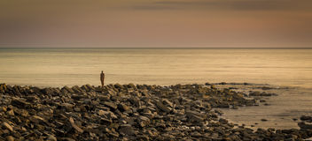 Lone figure stands looking out to sea Royalty Free Stock Photo