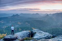 Alone figure watches the sunrise from sharp rock looking down at the wild landscape stock photo