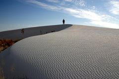 Lone Figure at White Sands. A lone figure stands silhouetted atop a dune at White Sands National Monument in New Mexico Royalty Free Stock Photos