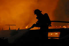 Lone firefighter. A firefighter battles a blaze at a house fire royalty free stock image