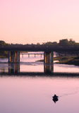 Lone Fisherman. On the river, with a traffic jam on the bridge behing him Stock Image