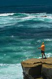 Lone Fisherman. A fisherman stands atop a rock outcropping to gain an advantage over the ocean's tide Stock Images