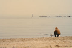 Lone fisherman on beach. Lone fisherman sat on deserted beach, calm Adriatic sea in background royalty free stock photography