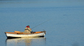 Lone Fisherman on a Calm Lake Stock Images
