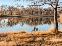 A Lone Fisherman on a Fall Day 1. A Fisherman Sitting Alone on a Fall Day at a Lake Royalty Free Stock Photo