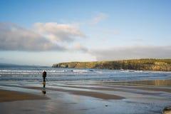 Lone fisherman fishing near the cliffs Stock Photography