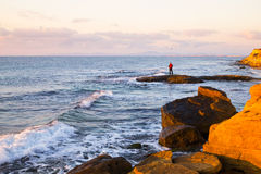 Lone fisherman fishing off rocks Stock Photo
