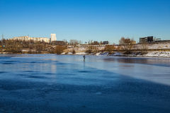 A lone fisherman on a frozen river Stock Image
