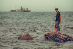 Lone fisherman gazes out at large fishing boat. Royalty Free Stock Images