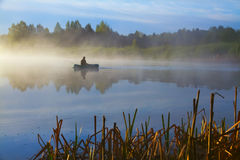 Lone fisherman on the lake early in the morning. Fisherman on the lake near Pskov city early in the morning Royalty Free Stock Photo