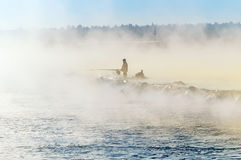A lone fisherman on the misty lake with a fishing rod, early in the morning Stock Images