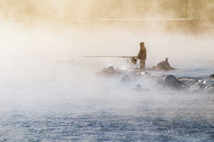 A lone fisherman on the misty lake with a fishing rod, early in the morning Royalty Free Stock Image