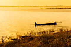 A lone fisherman moves out on a lake Royalty Free Stock Photography