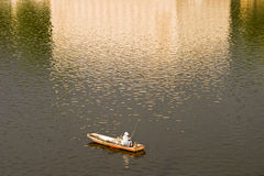 Lone Fisherman In Prague. A lone fisherman is fishing from a boat in the Vltava River in Prague. On the water behind him is an almost impressionist golden royalty free stock photography