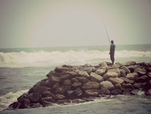 Lone fisherman sea waves rocks sunny warm fishing waves fishing Royalty Free Stock Photo