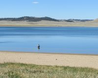Lone fisherman at Spinney Reservoir. One lonely fisherman in early morning at Spinney Mountain State Park, Colorado Stock Image