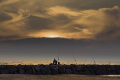 A lone fisherman at sunset. A fisherman is fishing at sunset and continue throughout the night stock image