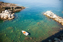 Lone fishing boat in Mediterranean emerald waters. On coastal Italian rocky lagoon Stock Images