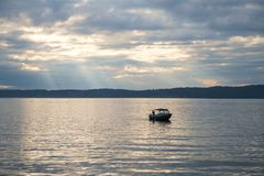 Lone fishing boat on Puget Sound. Redondo Beach, WA, USA Aug. 18, 2017: Lone fishing boat with a single person aboard on the reflective waters of Puget Sound Stock Image