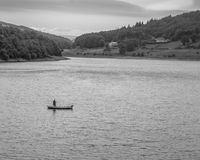 Lone fly fisherman on Ladybower Reservoir. Fly fisherman in a small lake boat, fisherman standing in the boat casting out line Stock Photo