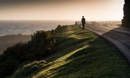 Lone girl walks along coast clifftop road Stock Image