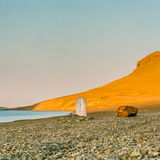 Lone grave-marker Arctic. A weather beaten grave market sits under a blue Arctic sky framed by golden hills lit by the sun royalty free stock photo