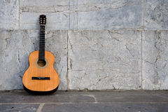 Lone Guitar. Single guitar left alone on a marble background. Shot evoking loneliness royalty free stock images