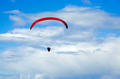 Lone Hang Glider. Soaring in clouds alone over the south Cornwall coast England Royalty Free Stock Images