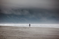 Lone hiker explores the beach in the fog Stock Photography