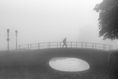 Lone hiker on sad morning walk over a bridge Stock Image