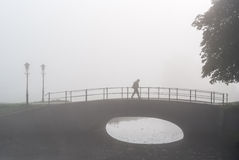 Lone hiker on sad morning walk over a bridge Royalty Free Stock Photography
