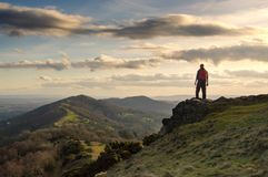 A lone hiker on top of a hill looking out on the ridge of the Malvern Hills, England. On a sunny winters day at sunset stock photo
