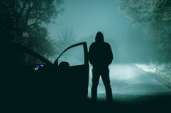 A lone, hooded figure standing next to a car looking at an empty. Misty winter country road silhouetted at night by car headlights. With a cold, muted grainy royalty free stock photos