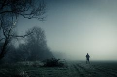A lone hooded figure standing on a path on a spooky misty night, with a cold blue edit. A lone hooded figure standing on a path on a spooky misty night, with a stock photos
