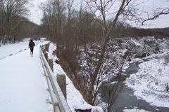 Lone Jogger. Photo of a jogger running along the C&O Canal towpath at Great Falls in Maryland in January.  Great Falls is on the Potomac river Stock Photography